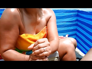 awesome woman gives beach handjob with big cumshot